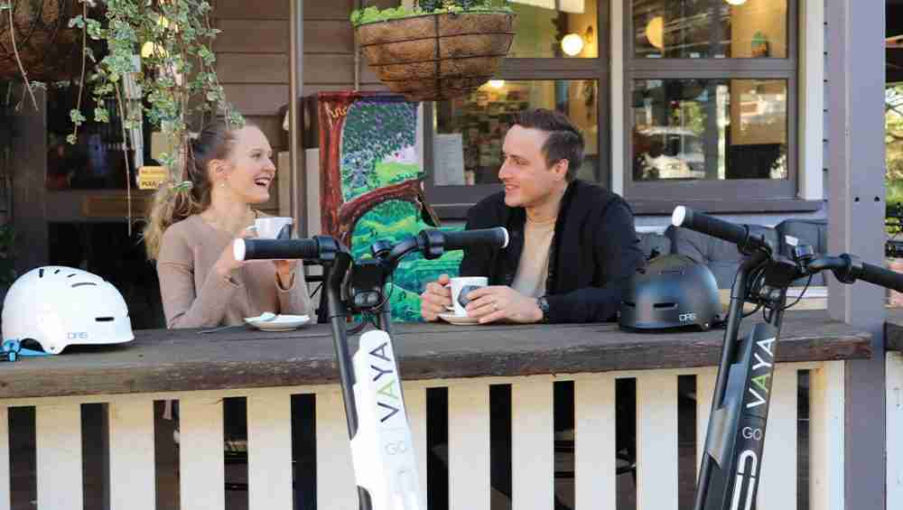 young couple drinking coffee at Brisbane cafe after riding VAYA Go Electric Scooters