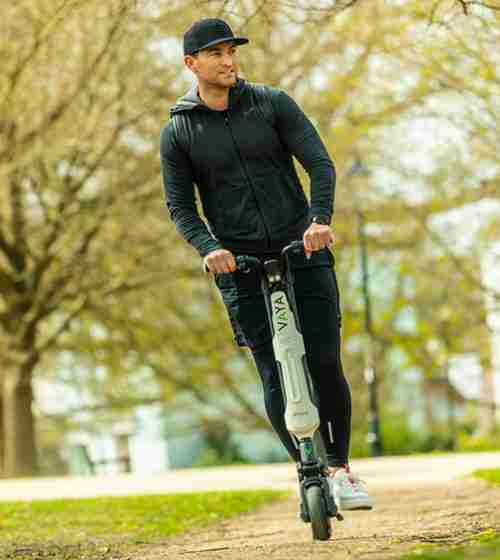 Young celebrity riding VAYA GO electric scooter through Hyde Park in London